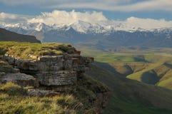 Paisaje panorámico hermoso de la montaña con los picos cubiertos por la nieve y las nubes Foto de archivo