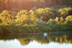 Paisaje pintoresco del bosque con el barco solo en el río Foto de archivo libre de regalías