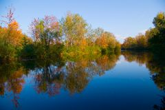 Paisaje pintoresco del otoño del río y de árboles brillantes Imagen de archivo libre de regalías
