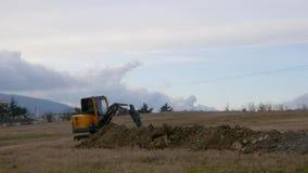 Paisaje que sorprende de los trabajos del excavador del tractor en foso del campo y de los empujes debajo del cielo azul ilimitad metrajes