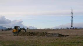 Paisaje que sorprende de los trabajos del excavador del tractor en foso del campo y de los empujes debajo del cielo azul ilimitad almacen de metraje de vídeo