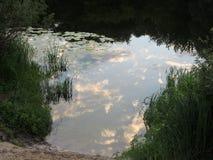 Paisaje que sorprende del campo con un río y una reflexión del cielo nublado Aldea ucraniana foto de archivo libre de regalías