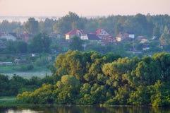 Paisaje rústico pintoresco del verano con el pequeño campo en el bosque cerca del río Fotos de archivo libres de regalías