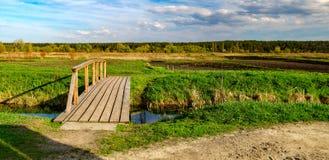 Paisaje rural con el pequeño río y el puente de madera Imagenes de archivo