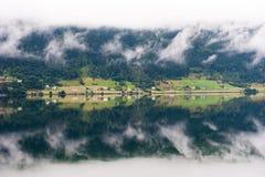 Paisaje rural con las casas, la cascada y las nubes, reflexión de espejo en el agua, Noruega Foto de archivo libre de regalías