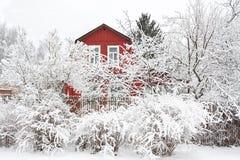 Paisaje rural del invierno con la casa y los árboles de madera en nieve Foto de archivo