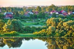Paisaje rural del verano con el pequeño campo en el bosque cerca del río Fotos de archivo