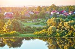 Paisaje rural del verano con el pequeño campo en el bosque cerca del río Imagen de archivo