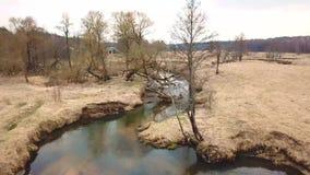 Paisaje rural en abril Pequeño río en primavera temprana almacen de metraje de vídeo