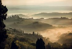 Paisaje rural en la salida del sol brumosa Colinas de Toscana con los árboles del jardín, chalets, colinas verdes, campo, Italia fotografía de archivo