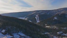 Paisaje rural en las montañas en invierno Casas nevadas en pueblo en la nieve de una altura Vuelo sobre metrajes
