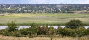 Paisaje rural que pasa por alto el río con los prados del agua y las casas rurales Imágenes de archivo libres de regalías