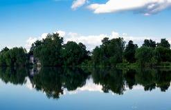 Paisaje ruso hermoso reflejado en el lago Árboles verdes y cielo azul Imagen de archivo