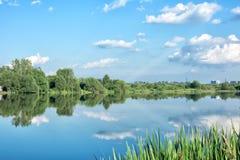 Paisaje ruso hermoso reflejado en el lago Árboles verdes y cielo azul Fotos de archivo libres de regalías