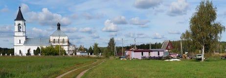 Paisaje ruso rústico típico - una iglesia al lado de campos, camino Foto de archivo