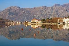 Paisaje simétrico hermoso donde las montañas y la costa se reflejan en agua Montenegro, bahía de Kotor, ciudad de Dobrota imágenes de archivo libres de regalías