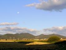 Paisaje soleado con una Luna Llena en el cielo Imagen de archivo libre de regalías