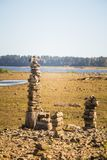 Paisaje soleado de la orilla de una cama y de las rocas de río secada Construcciones de equilibrio de piedra cerca del río Imagen de archivo