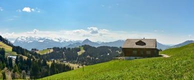 Paisaje suizo hermoso con la choza de la montaña y las montañas nevosas en Imagen de archivo