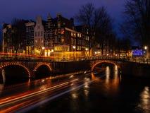 Paisaje típico del canal de Amsterdam en la noche con los rastros ligeros y agua reflectora fotos de archivo