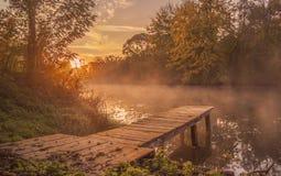 Paisaje tienda un puente sobre la helada de madera en la orilla del río en el morni Fotos de archivo