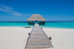 Paisaje tropical con el puente de madera y la choza en el agua en Maldivas Imágenes de archivo libres de regalías