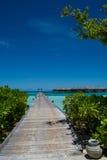 Paisaje tropical con los chalets del puente de madera y del agua en Maldivas Fotografía de archivo libre de regalías