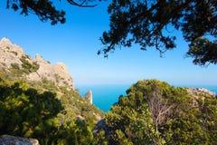 Paisaje tropical hermoso con el top de la montaña que pasa por alto las rocas y el mar, enmarcado por las ramas del pino, teñidas Imagen de archivo