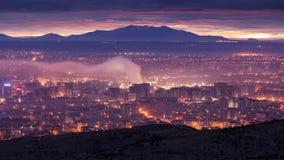 Paisaje urbano bajo humo durante puesta del sol? en Almaty Fotografía de archivo libre de regalías