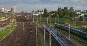 Paisaje urbano con muchas vías ferroviarias en el primero plano y el movimiento del tren de pasajeros del viajero almacen de video