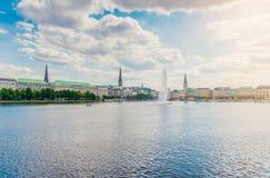 Paisaje urbano de Hamburgo el día soleado contra el cielo azul con el lago Alster en primero plano imagen de archivo libre de regalías