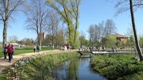 Paisaje urbano de la ciudad Wittstock Dosse en Alemania Gente que camina a través de pequeño parque con fluir de la corriente Flo metrajes