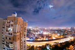 Paisaje urbano de la noche del noida con el rascacielos, las nubes de la monzón y el MOO Foto de archivo libre de regalías