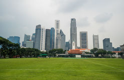 Paisaje urbano de Singapur con el campo de fútbol y los altos edificios comerciales Fotos de archivo libres de regalías