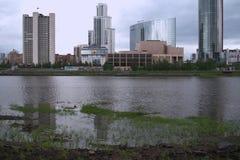 Paisaje urbano En el plan cercano es un banco rocoso del río, hierba en el agua fotografía de archivo libre de regalías