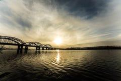 Paisaje urbano increíblemente hermoso Puesta del sol El puente sobre el río Foto de archivo