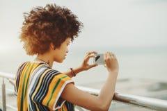 Paisaje urbano joven del tiroteo de la muchacha del ébano en su teléfono Fotos de archivo libres de regalías