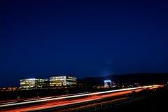Paisaje urbano ocupado de la autopista sin peaje y de la oficina de la noche de Silicon Valley Fotografía de archivo libre de regalías