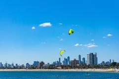 Paisaje urbano urbano pintoresco con las personas que practica surf de la cometa en la playa Fotos de archivo libres de regalías