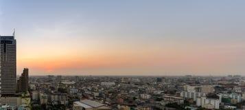 Paisaje urbano: Puesta del sol y la opinión de la ciudad de los edificios de los aumentos pequeños en vagos Fotos de archivo