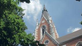 Paisaje urbano tranquilo con la iglesia grande del ladrillo rojo en ciudad, inclinación encima de la visión, follaje de los árbol metrajes