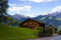 Paisaje urbano: una casa en el fondo de montañas Fotografía de archivo