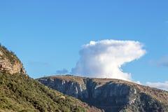 Paisaje verde de Rocky Cliff Against Blue Cloudy Sky de los árboles imagen de archivo
