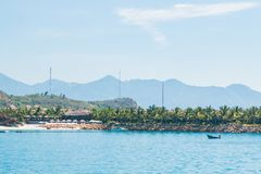 Paisaje, visión desde el mar, playa blanca, palmeras, montañas, barco, avión en el cielo, Vietnam Hotel de cinco estrellas foto de archivo libre de regalías