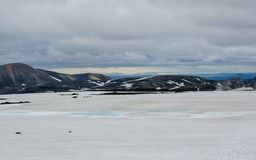 Paisaje volcánico con dos lagos azules en un centro del campo de lava cubierto con la nieve, pista de senderismo de Laugavegur, n foto de archivo
