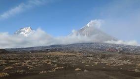 Paisaje volcánico hermoso de Kamchatka: Kamen Volcano y erupción del volcán de Klyuchevskoy almacen de metraje de vídeo