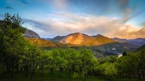 Paisajes de la primavera Una hermosa vista de las monta?as y del lago Nubes muy interesantes y cielo azul en el fondo imagenes de archivo