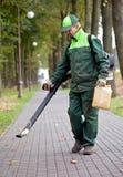 Paisajista que limpia la pista usando ventilador de hoja Imagenes de archivo