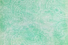 Paisley patterned background in shades of green. A pale green shabby background covered in fancy dark green paisley shapes Stock Photography