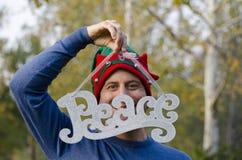 Paix à Noël - équipez la dissimulation derrière la paix de mot utilisant un chapeau de Noël Photographie stock